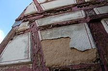 Angesichts der mit HLZ-Steinen ausgemauerten Fachwerkfelder in diesem Bereich und viel zu dick darüber aufgeputzten, stark frostgeschädigten Putzkissen sind hier auf alle Fälle Eingriffe für Reparaturen zu erwarten. / ehemaliges Gasthaus zum Lamm in 74229 Oedheim (28.08.2012)